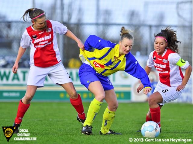 De kwaliteit van het shirtje van Berkel speelster Melissa van den Berg wordt door Lotte Verleng van RCL uitgestest op maximale rekbaarheid. Aanvoerster Stephanie Hartogs van RCL kijkt toe om later in te grijpen.