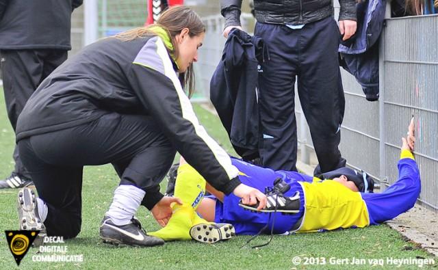 Fysiotherapeute Yvette Duran van Berkel heeft net de linkerschoen van de voet van Nadine Bier verwijderd die kermend van de pijn naast de lijn op het veld ligt.