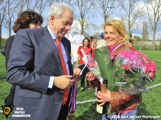 Coach Carola van der Laan ontvangt van Teo Oortman van de KNVB de kampioensmedaille.