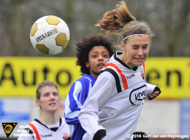 Lisa Stigter van Jodan Boys kopt de bal net weg voor de inkomende Elsa Pinto van SVS. Op de achtergrond kijkt Toos den Oudsten goedkeurend toe.